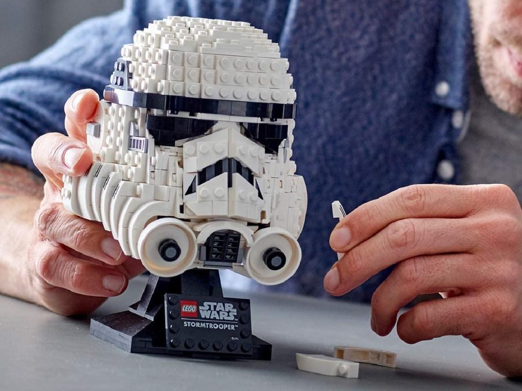 man building Star Wars stormstrooper LEGO helmet