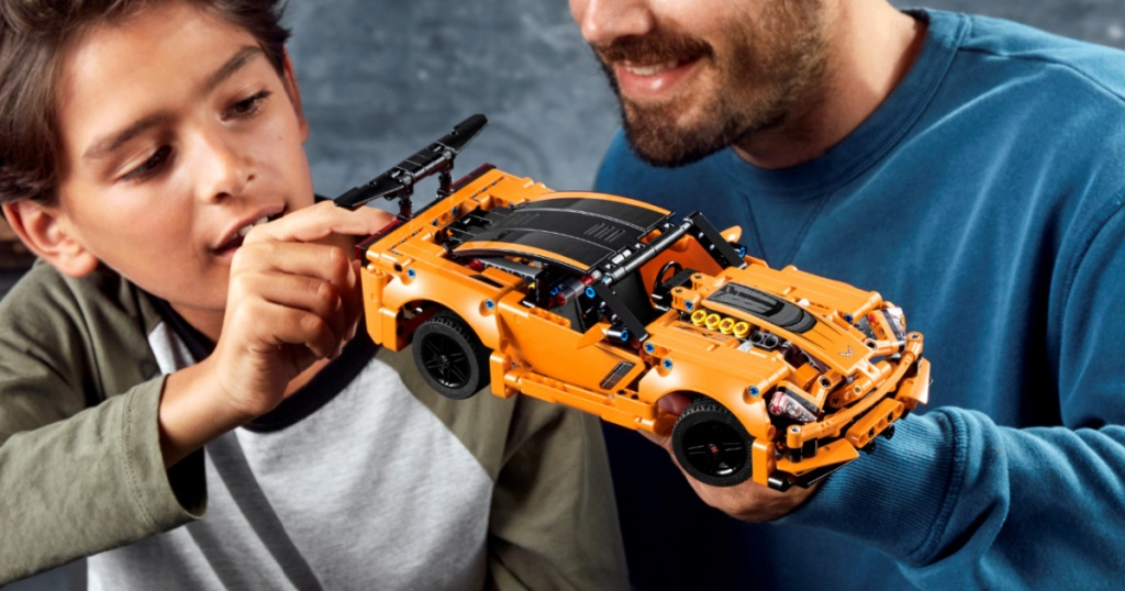 man and boy playing with toy building car