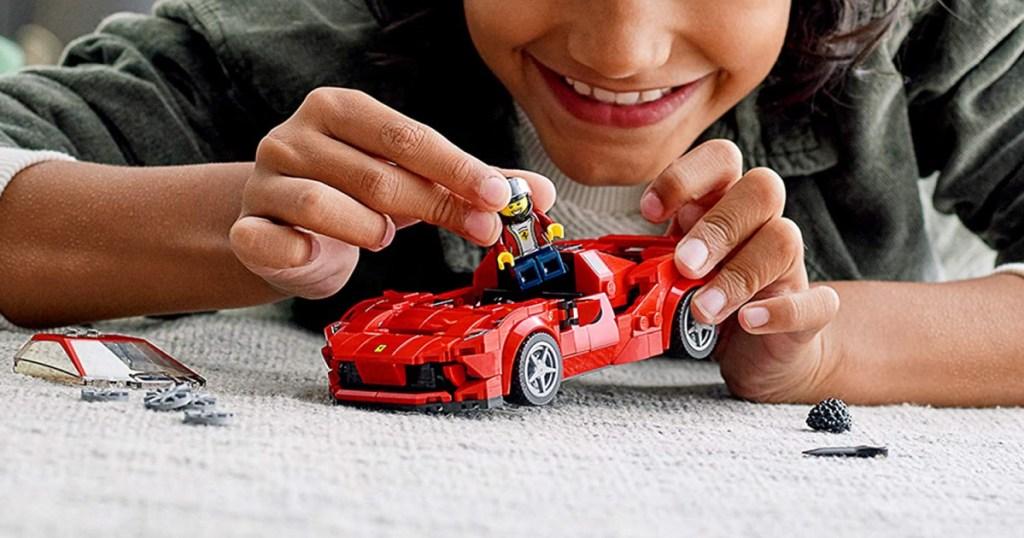 boy playing with LEGO speed ferrari