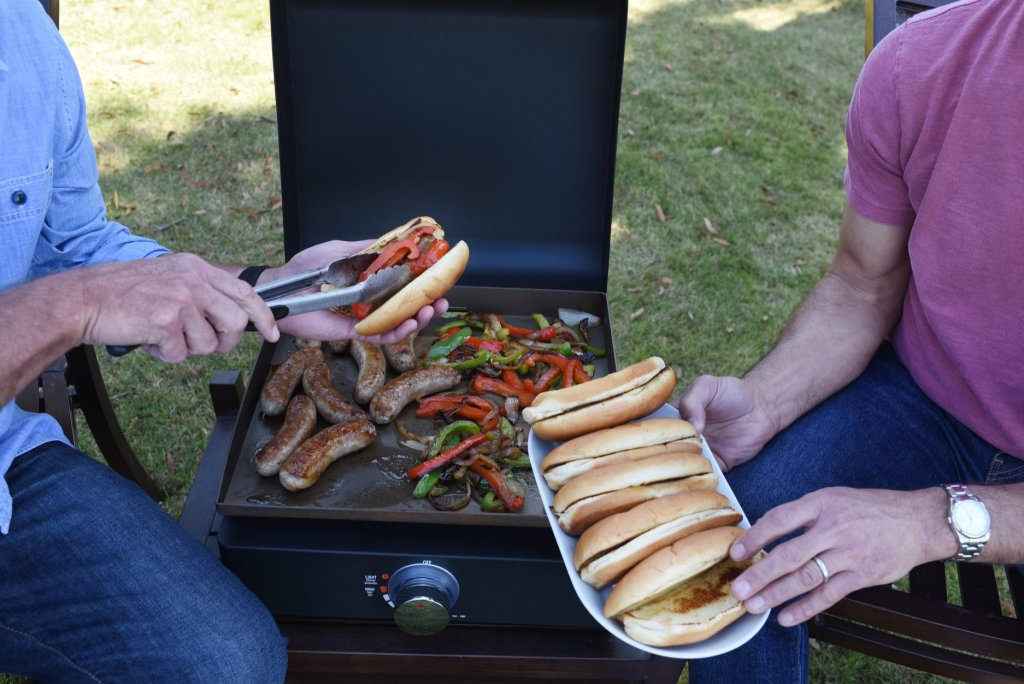 two people next to a portable grill with plates of food