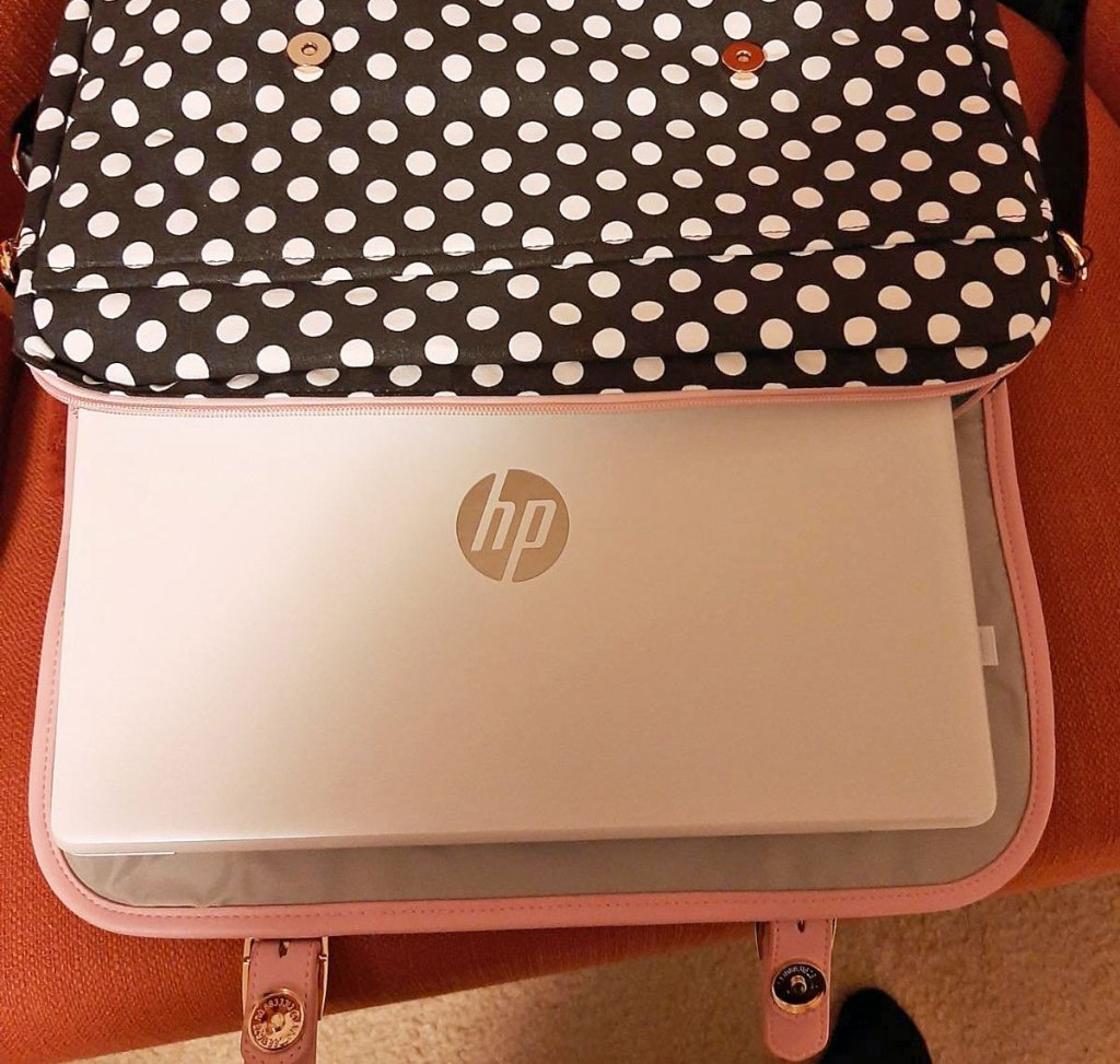 silver HP laptop sliding into a black and white polka dot print laptop case