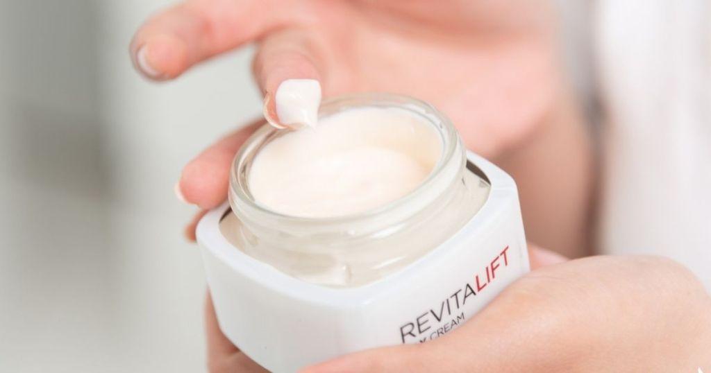 woman's hand taking cream from RevitaLift Jar