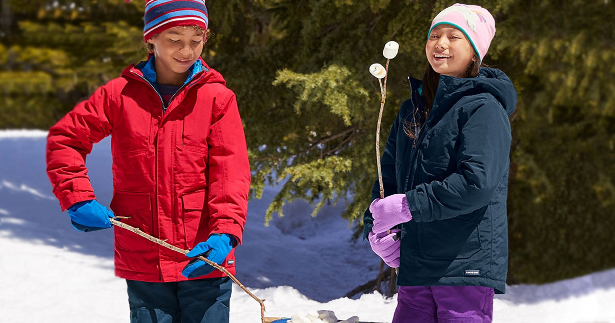 two kids wearing winter jackets and accessories while in snow roasting marshmallows