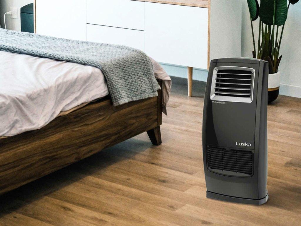 black lasko electric heater in bedroom next to bed