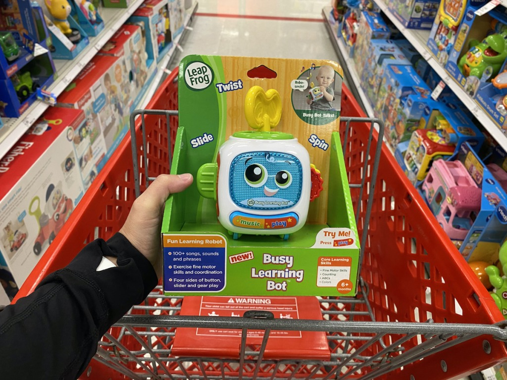 hand holding LeapFrog Busy Learning Bot in target cart