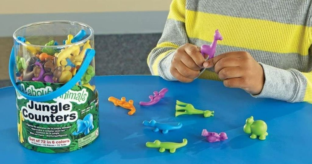 child playing with bucket of animal counters on a blue table