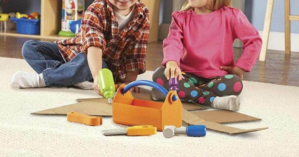 Two kids sitting on the floor playing with tools