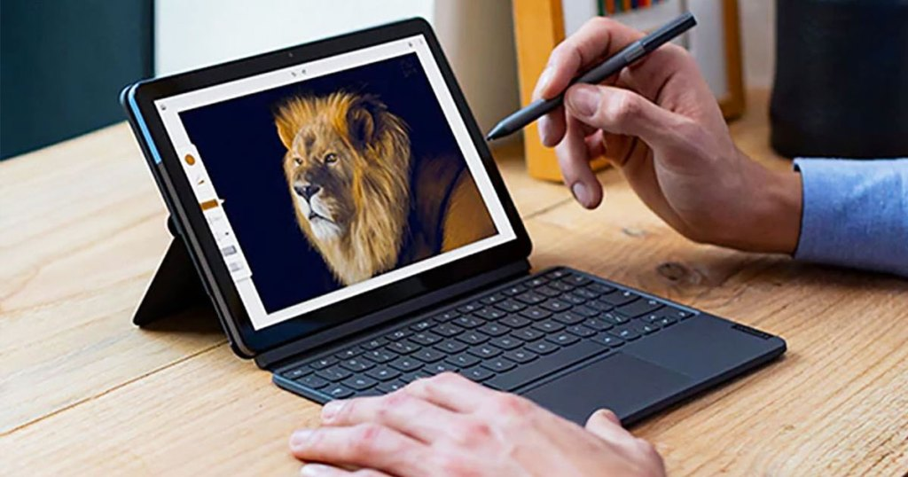 man using a stylus pen to work on lenovo chromebook tablet on wood desk