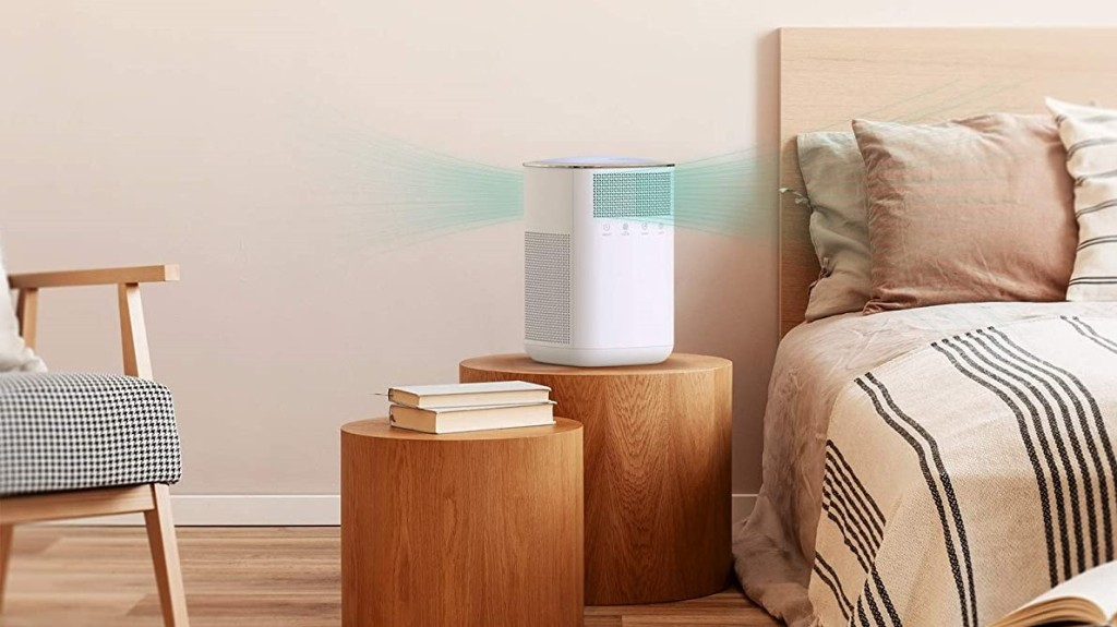 bedroom with a bed, nightstands, air purifier and chair