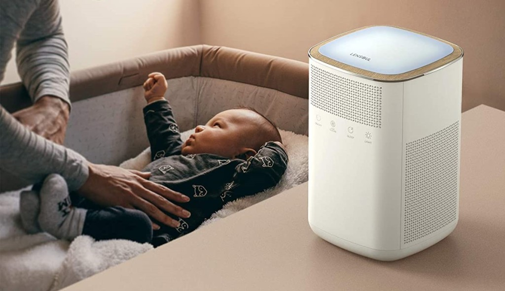 air purifier on a table next to a baby crib