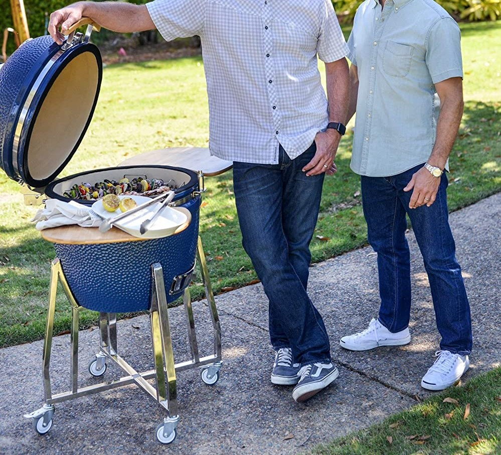 two men standing next to an open grill