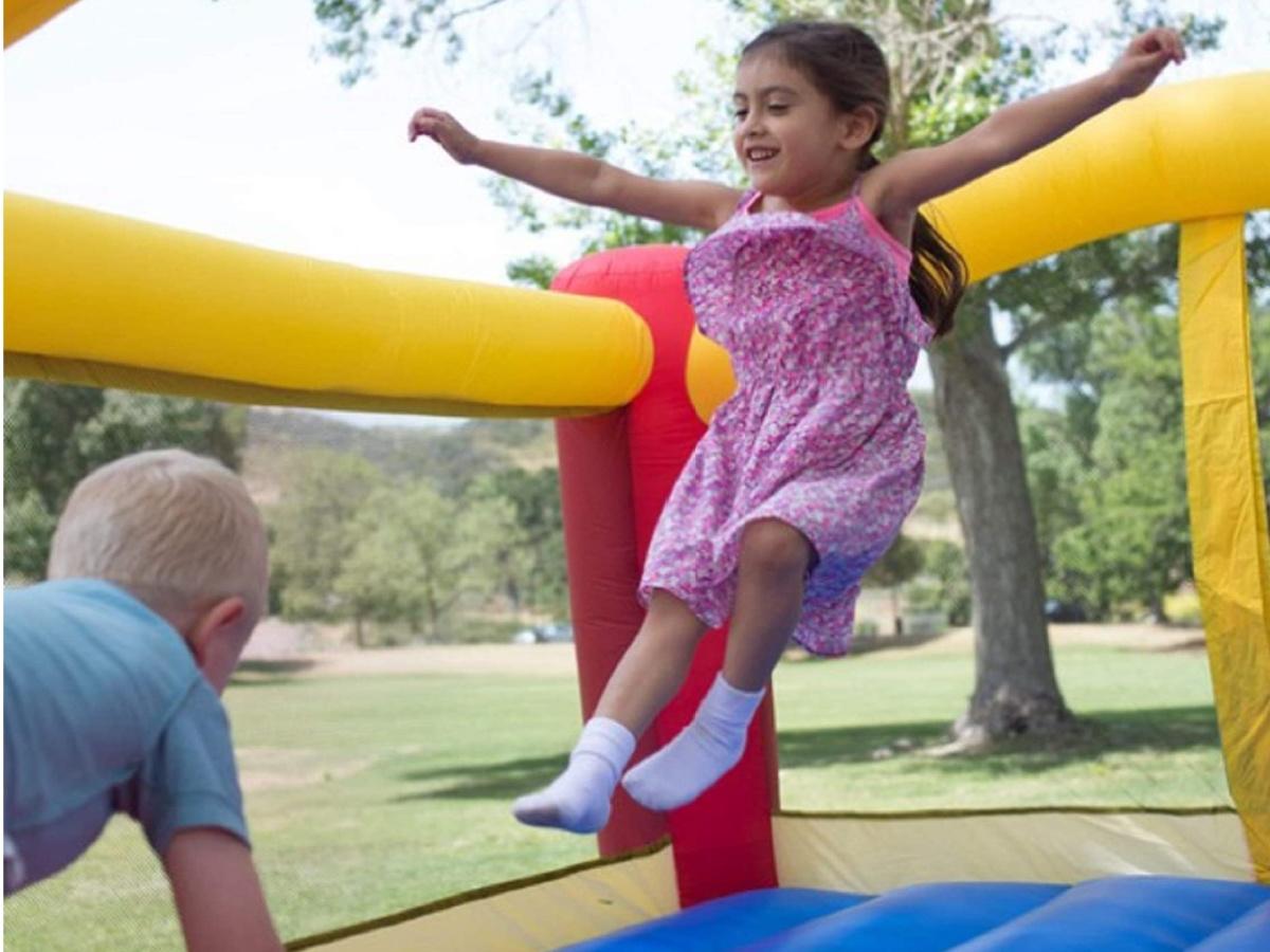 little girl wearing bouncing in a little tikes bounce