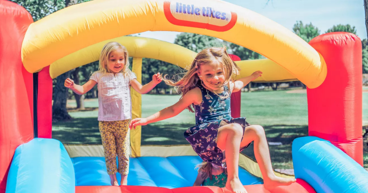 two little girls bouncing in a little tikes bounce house