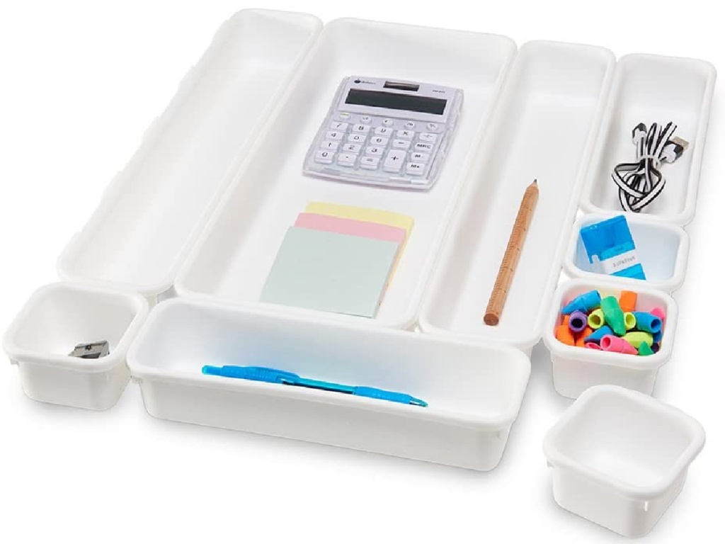 white organizational bins filled with pens, calculator, and more office supplies