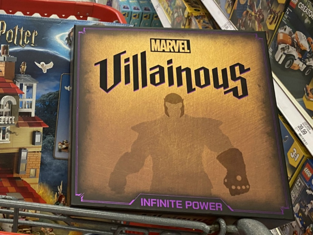 Marvel themed board game in a red shopping cart near other toys