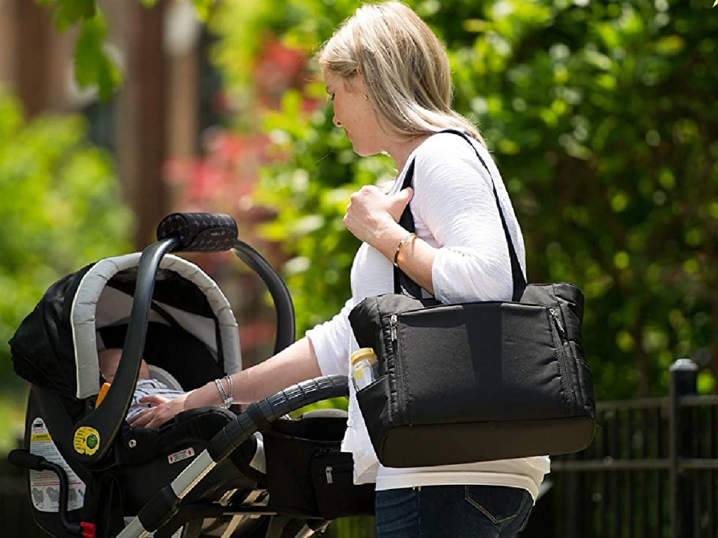 woman holding black tote bag with milk bottle and baby in stroller outside