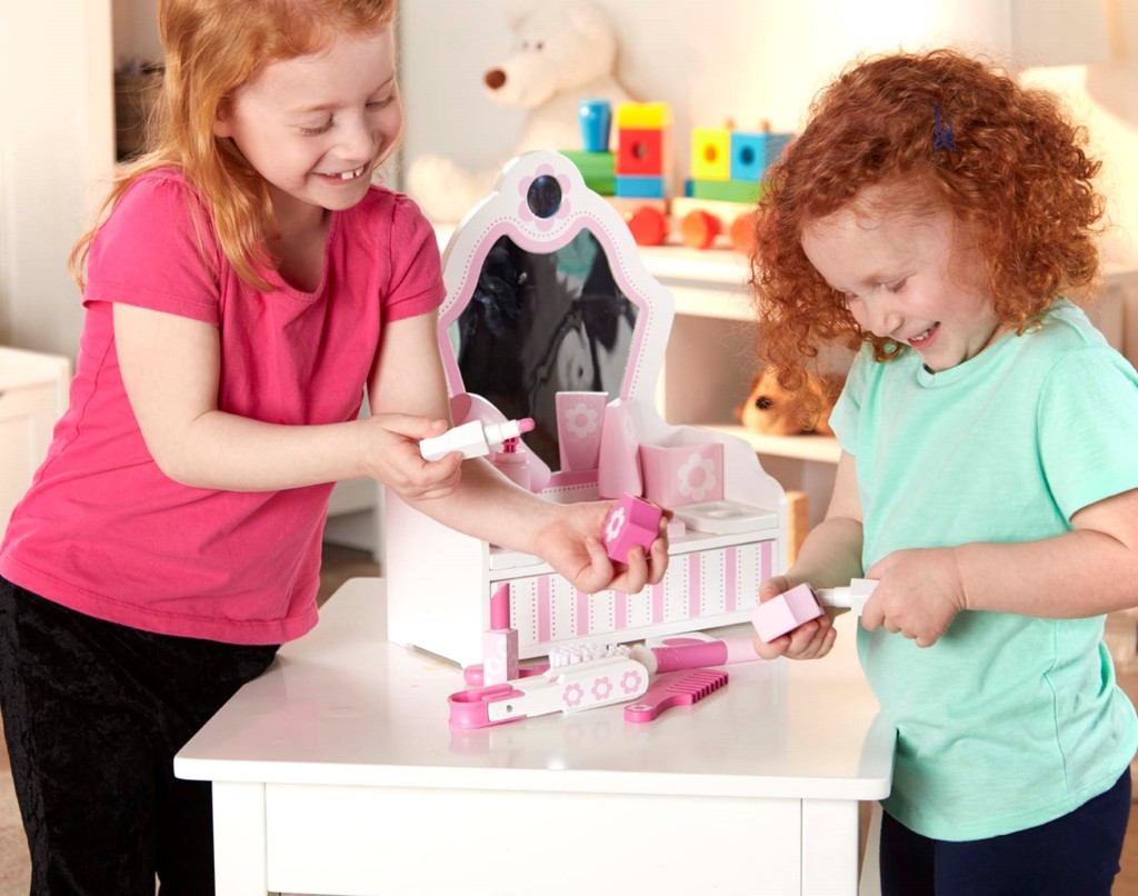 two girls playing with a beauty salon set