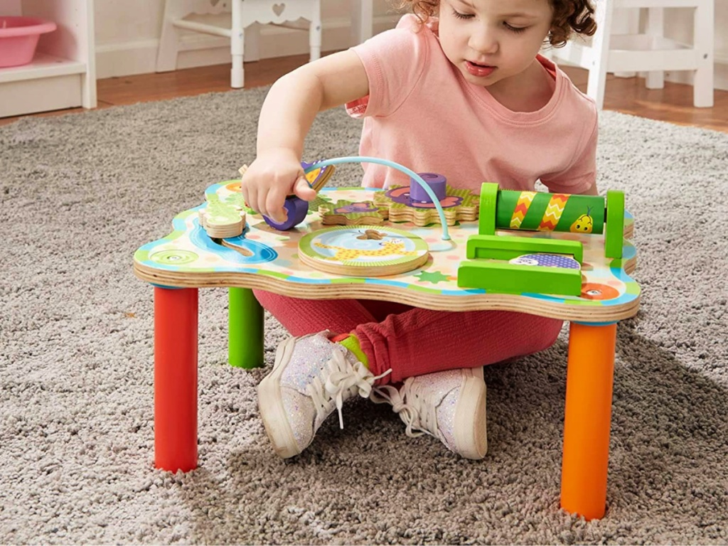 little girl playing with a Melissa & Doug Jungle Activity Table