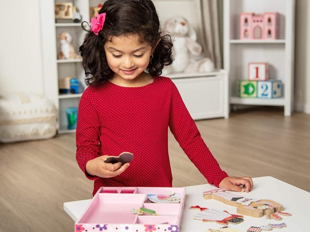 girl in red shirt playing with magnetic doll and accesories