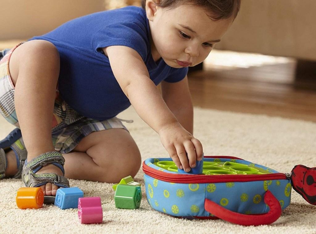 toddler boy putting shapes in a sorter
