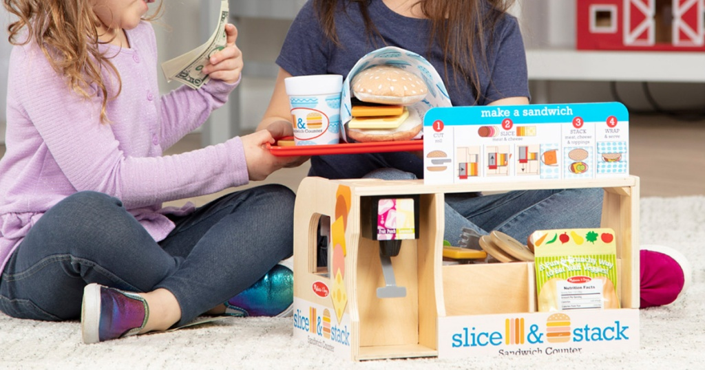 two girls playing with sandwich playset on floor