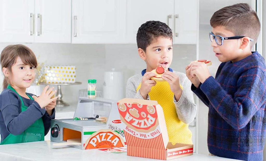 three kids in kitchen playing with pizza counter playset
