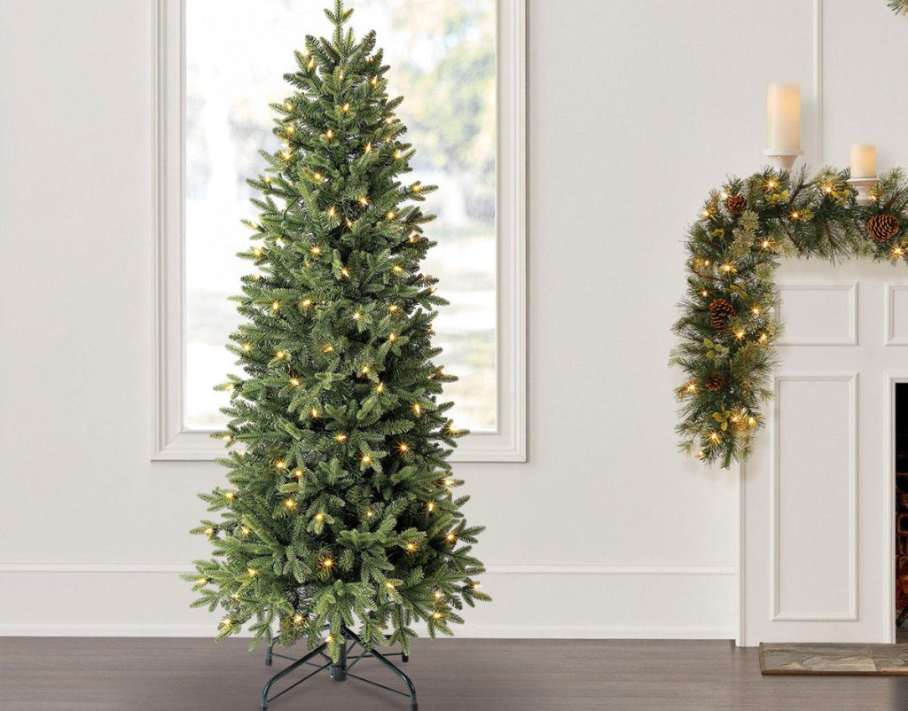 christmas tree with white lights in front of window and near a decorated fireplace mantel