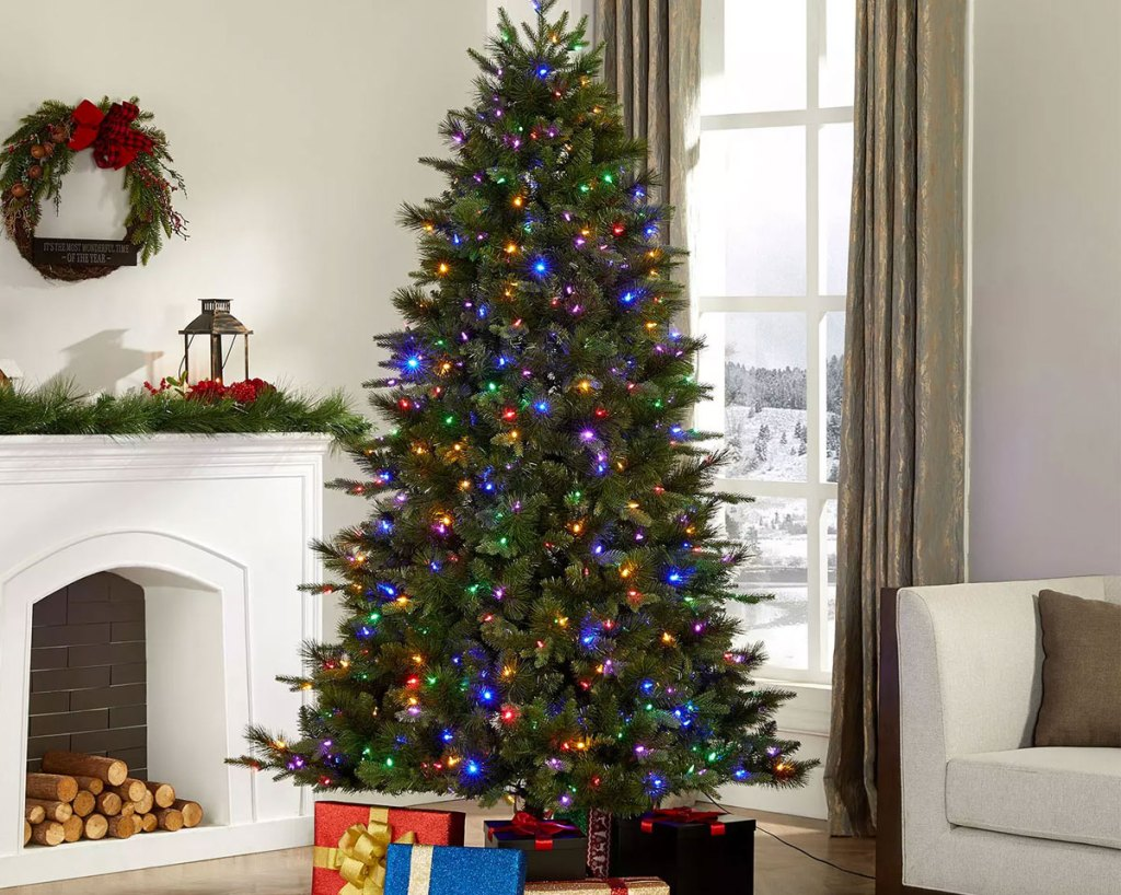 christmas tree in living room with multi-colored lights and wrapped presents at base