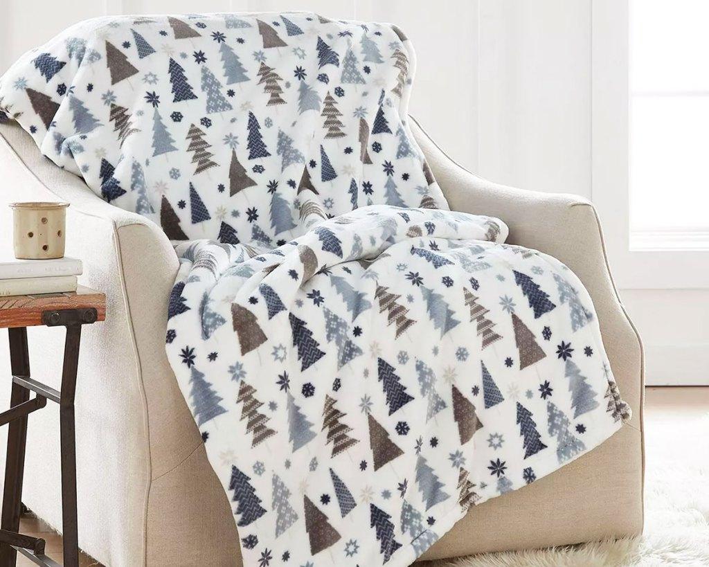 christmas tree print throw blanket draped on a cream chair