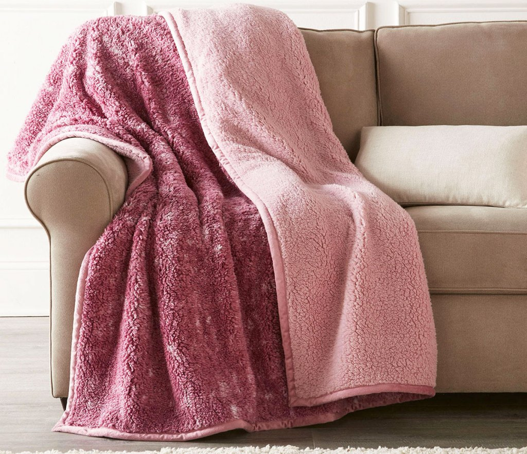 reversible pink sherpa throw draped on a cream color couch
