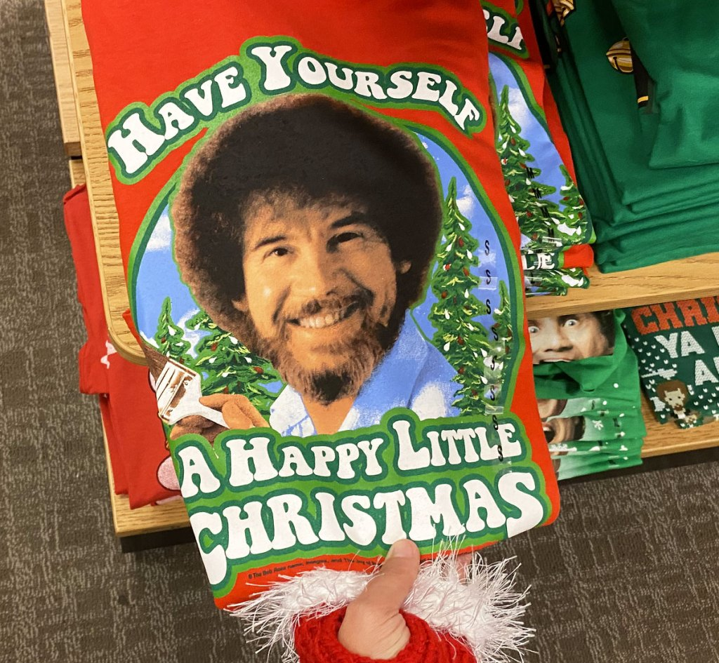 person with red santa glove holding a red bob ross christmas graphic tee