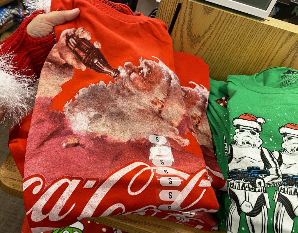 person in red and white santa glove holding red coco cola graphic tee with santa drinking coke