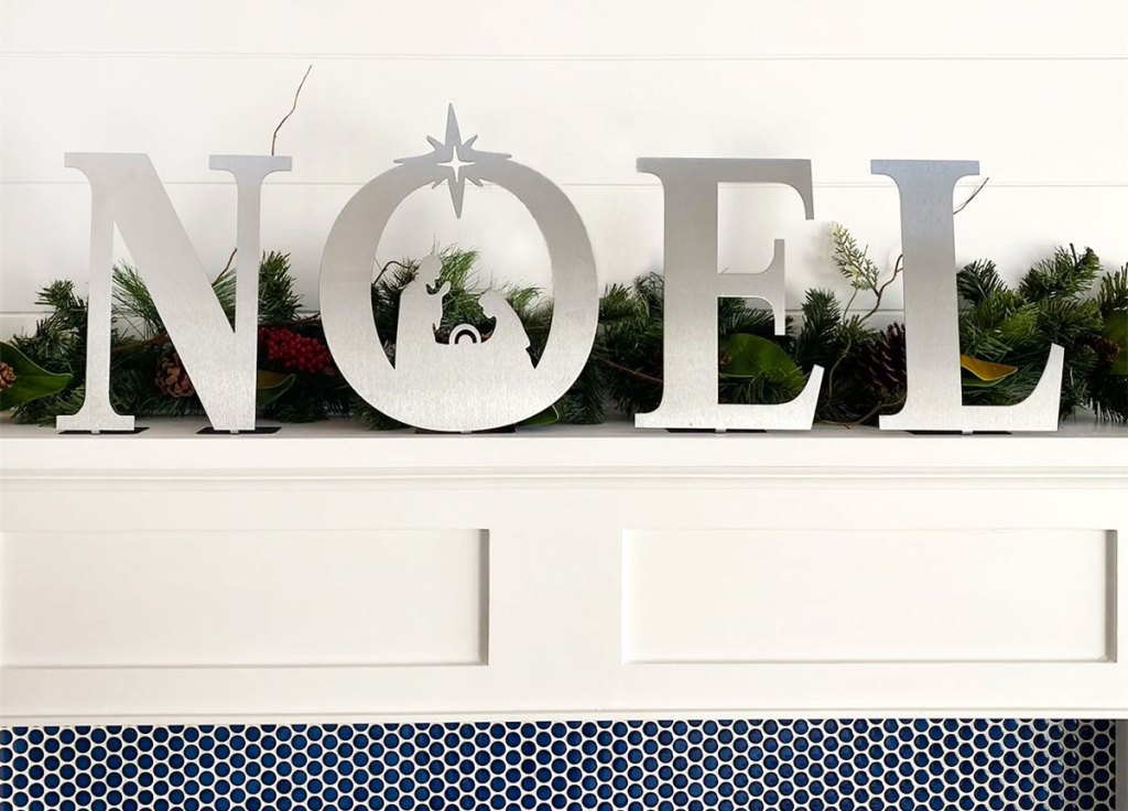 metal noel letters on mantel with nativity scene inside the letter O