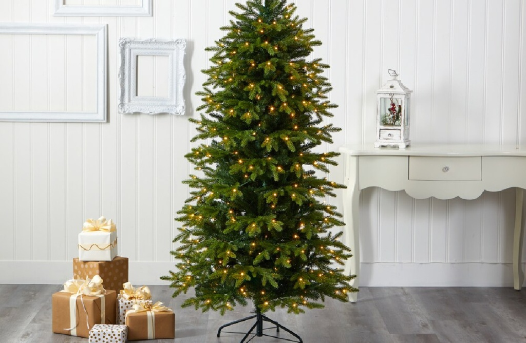 large lit christmas tree next to presents and a white console table