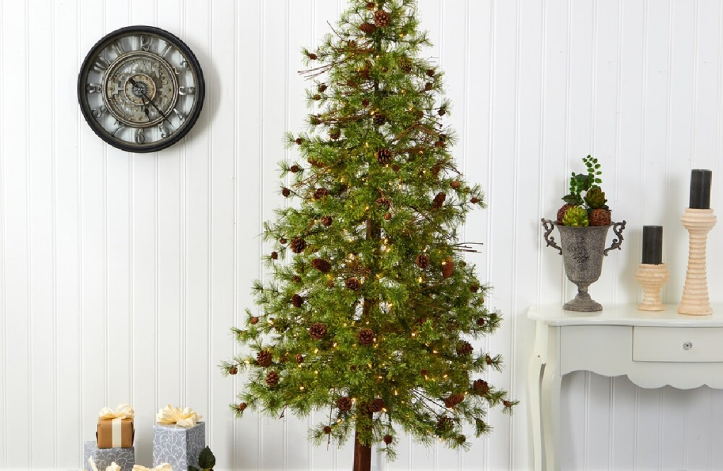skinny tall christmas tree with small pinecones in a living space