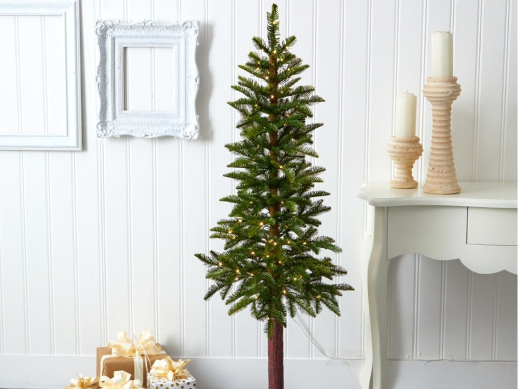 5' plain christmas tree next to a white table with presents underneath