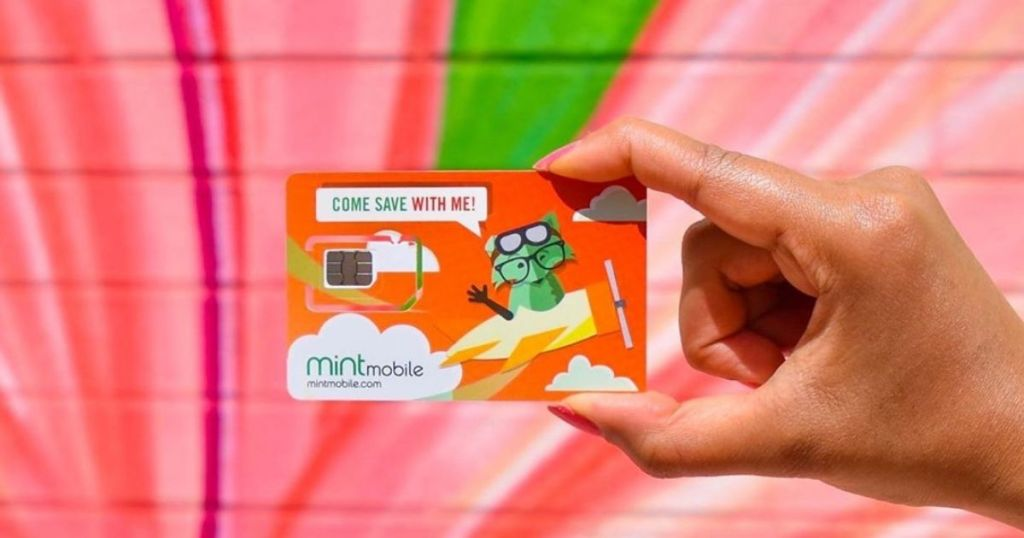hand holding mint mobile card on pint background