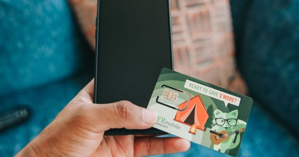 hand holding Mint Mobile Card and phone