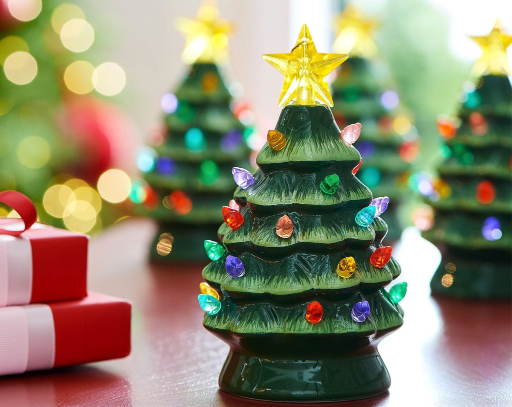 green mini ceramic tree ornament with multicolor lights on table in front of more tree ornaments