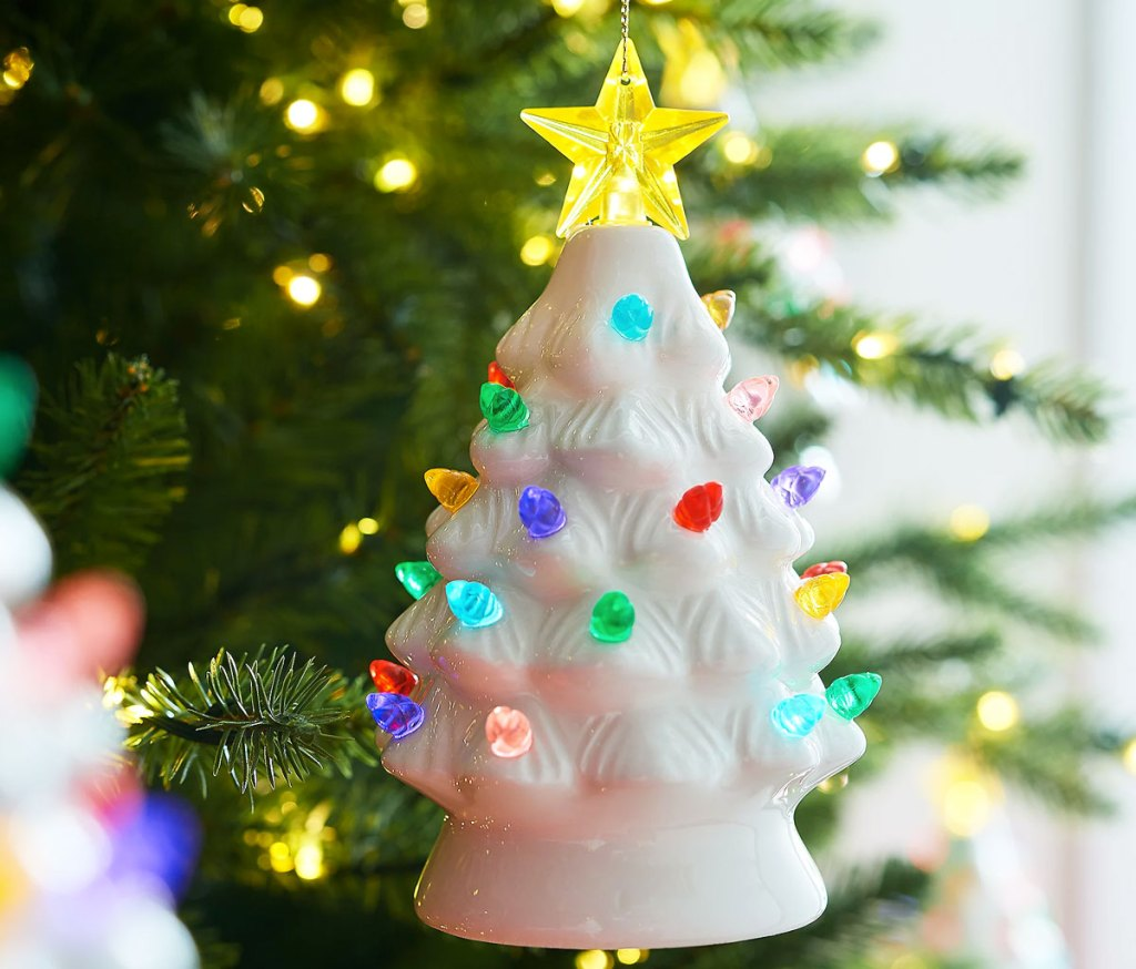 white mini ceramic tree ornament with mutlicolor lights hanging on christmas tree
