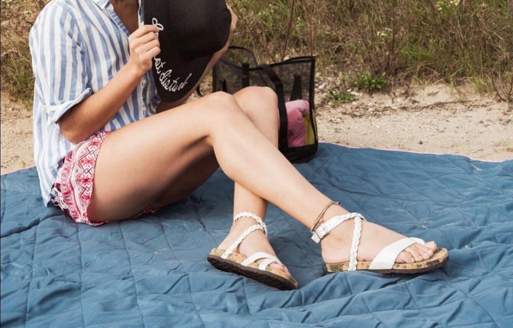 woman sitting on a beach blanket