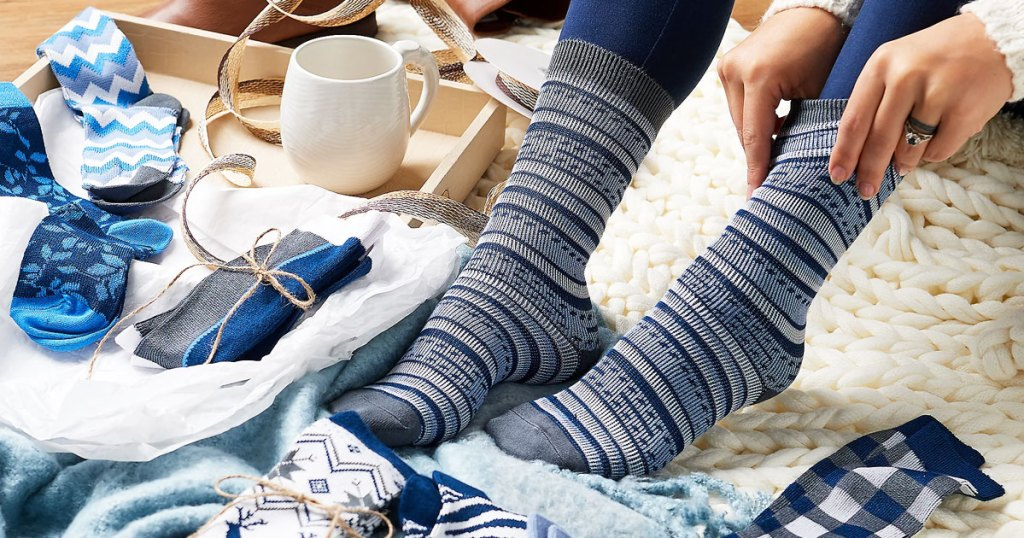 woman putting on a pair of striped boot socks with other pairs of socks around her