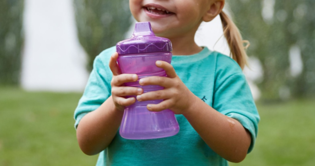 young girl smiling and holding purple sippy cup outside