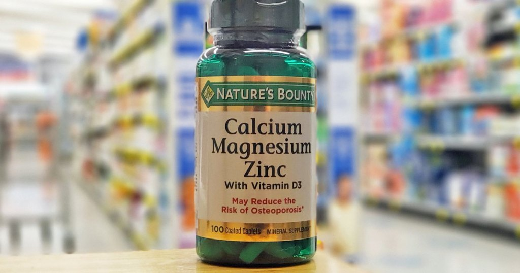 green bottle of Nature's Bounty calcium, magnesium, and znic supplement on wood table at store