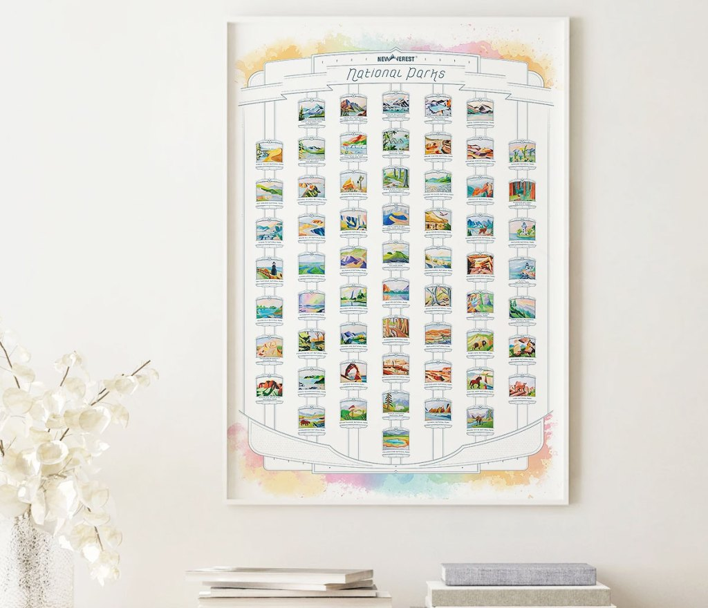 white national parks scratch off poster on wall near vase of white flowers
