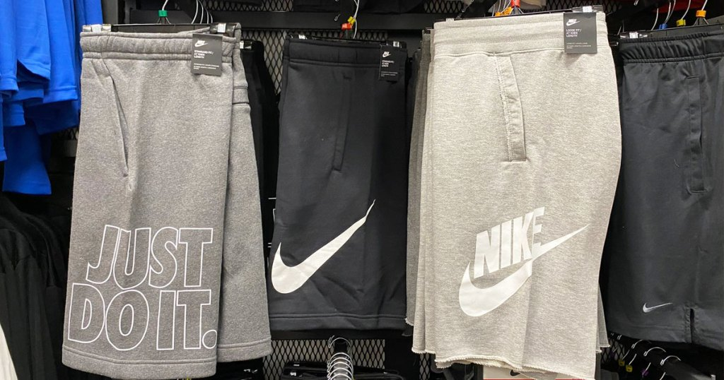 pairs of nike basketball shorts on hangers on store display wall