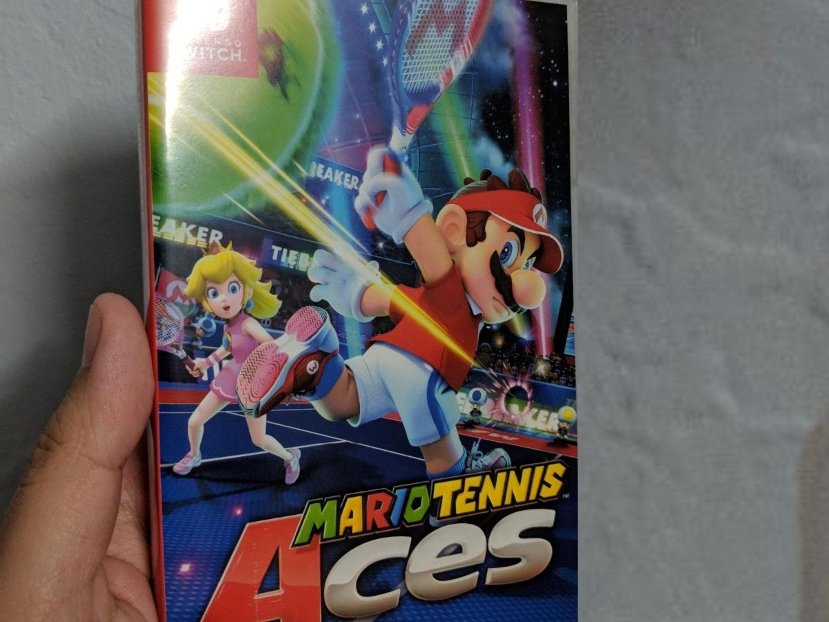 hand holding Mario Tennis Aces game