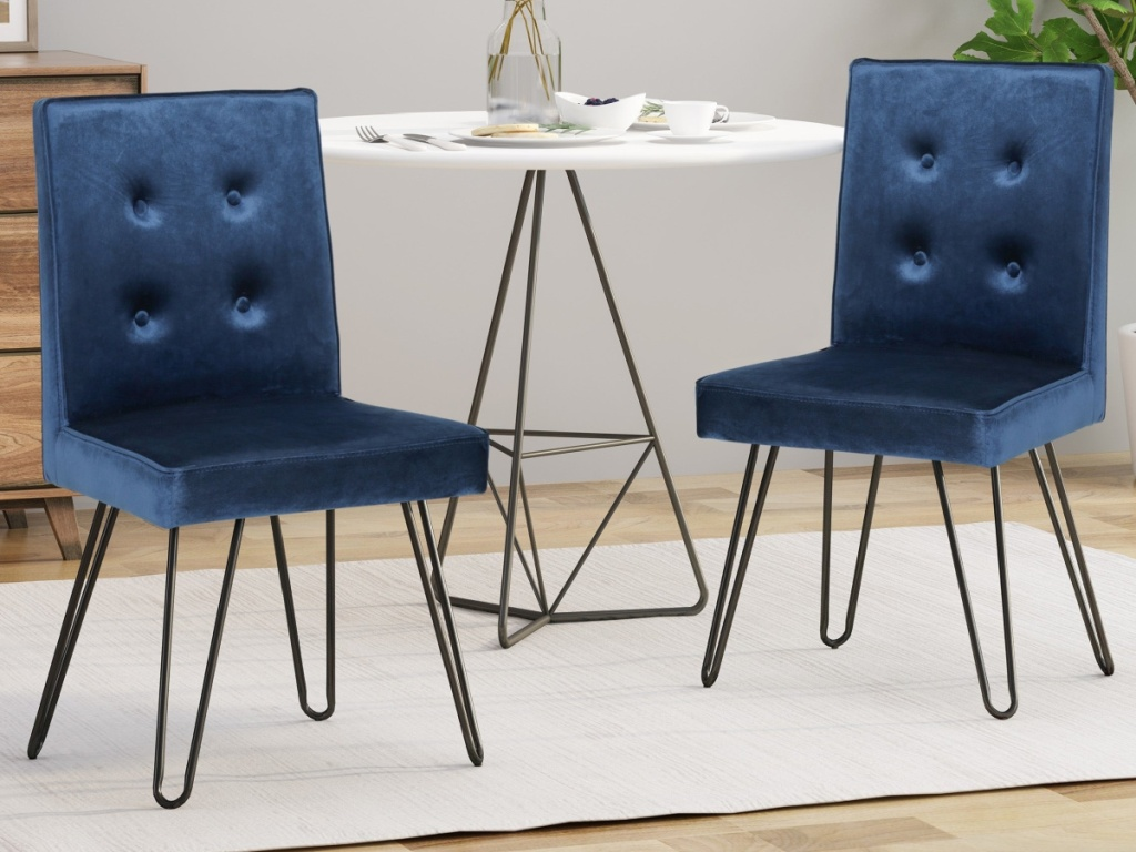 two blue metal dining chairs and table in home