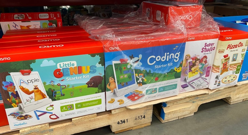 red boxes of osmo stem games staked on wood pallets on floor