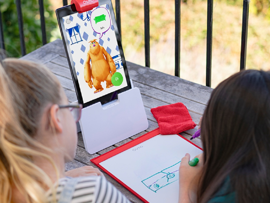 two girls playing with STEM electronic learning kit on table outside